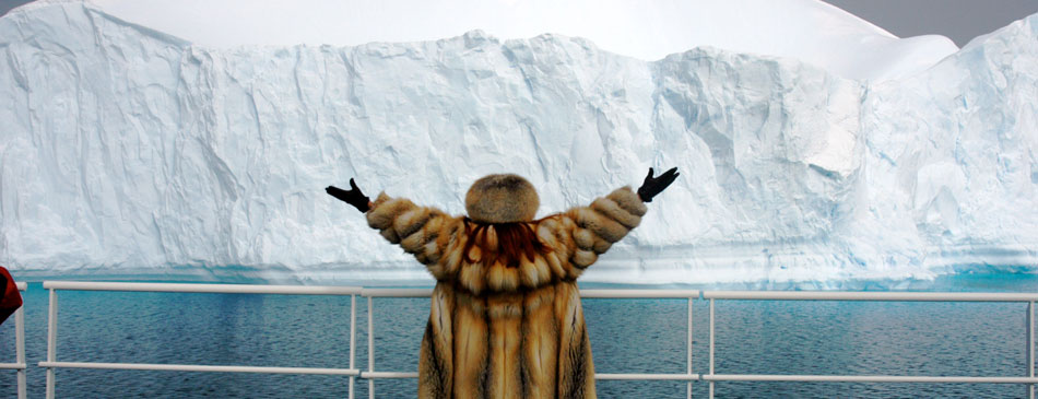 Woman joyful with arms open as the ship passes a Glacier